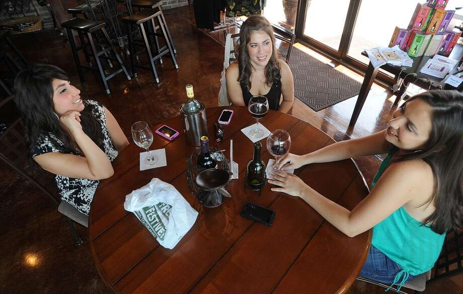 From left, Kourtney Clark, Melissa Saldana and Laura Ibara enjoy the classic atmosphere and a few glasses of wine at D'Vine Wine Winery in Beaumont. Guiseppe Barranco/The Enterprise Photo: Guiseppe Barranco/The Enterprise
