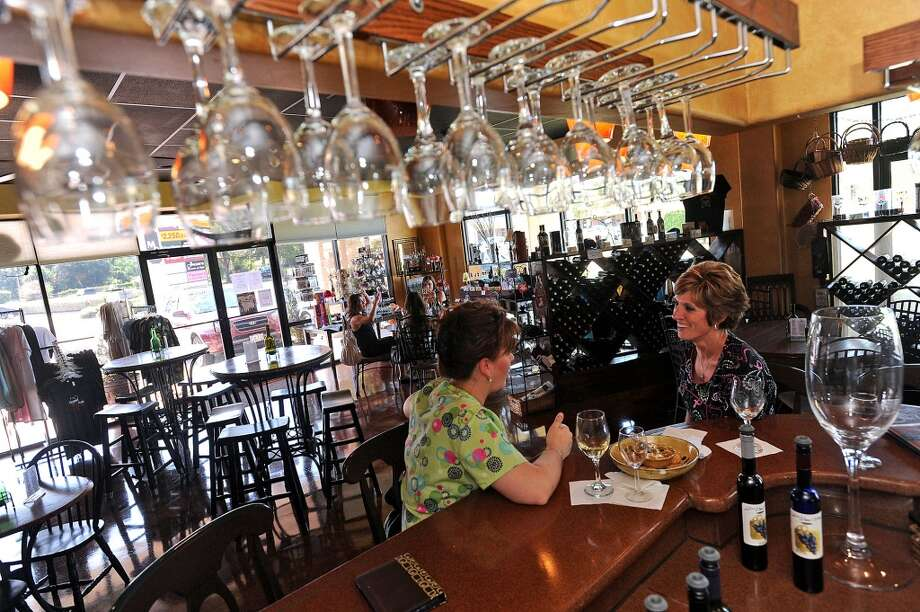 From left, Jennifer Hignett and Amanda Daigle enjoy an appetizer and a few glasses of wine at D'Vine Wine Winery in Beaumont. Guiseppe Barranco/The Enterprise Photo: Guiseppe Barranco/The Enterprise