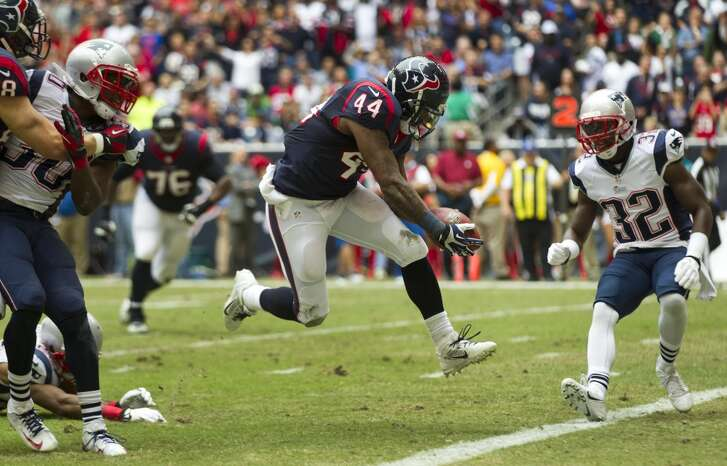 Texans running back Ben Tate (44) leaps across the the goal line past New England Patriots free safety Devin McCourty (32) for an 8-yard touchdown run during the first quarter.