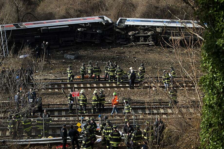 Emergency personnel respond to the scene of a Metro-North passenger train derailment in the Bronx borough of New York, Sunday, Dec. 1, 2013. The train derailed on a curved section of track in the Bronx on Sunday morning, coming to rest just inches from the water and causing multiple fatalities and dozens of injuries, authorities said. (AP Photo/John Minchillo) Photo: John Minchillo, Associated Press