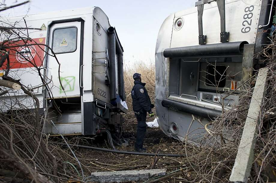 A police officer looks over a body at the wreckage of a Metro-North Railroad commuter train after it derailed in the southwest Bronx, across the Hudson River from the northern tip of Manhattan Island in New York, Dec. 1, 2013. At least four people were killed and more than 60 injured, 11 critically, officials said. (Gregg Vigliotti/The New York Times) Photo: Gregg Vigliotti, New York Times