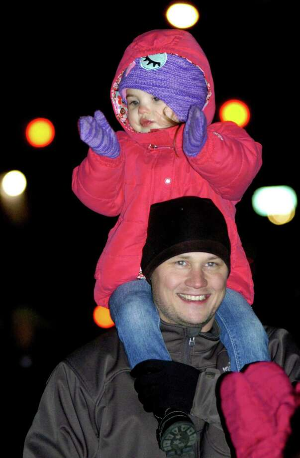 Perched on the shoulders of her dad, Tom Buccieri of New Milford, Brooke Buccieri, 3, of New Milford offers hearty applause for a well-decorated firetruck Saturday, Nov. 30, 2013 on the New Milford Village Green during the Greater New Milford Chamber of Commerce's annual Festival of Lights. Photo: Norm Cummings / The News-Times