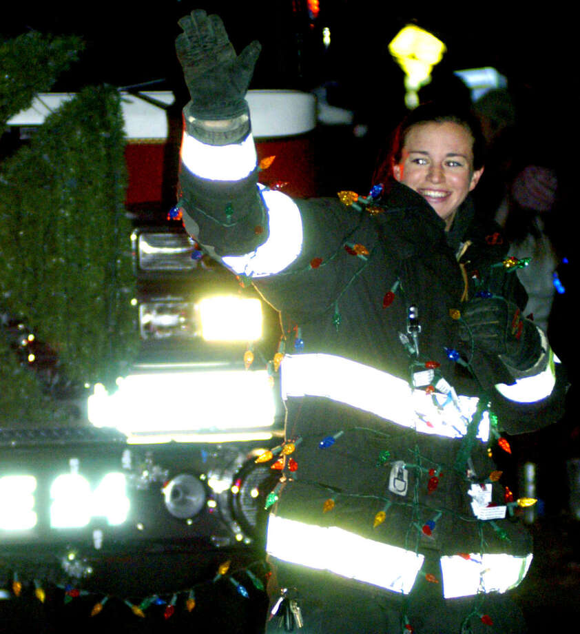 Probationary Water Witch Hose Co. No. 2 firefighter Maureen Hickey waves to the crowd as she leads her department's decorated firetruck on the parade route, Saturday, Nov. 30, 2013 along the New Milford Village Green during the Greater New Milford Chamber of Commerce's annual Festival of Lights. Photo: Norm Cummings / The News-Times