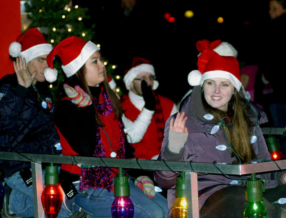 Santa's elves, hitching a ride aboard a Sherman firetruck, wave to the throng Saturday, Nov. 30, 2013 along the New Milford Village Green during the Greater New Milford Chamber of Commerce's annual Festival of Lights. Photo: Norm Cummings / The News-Times