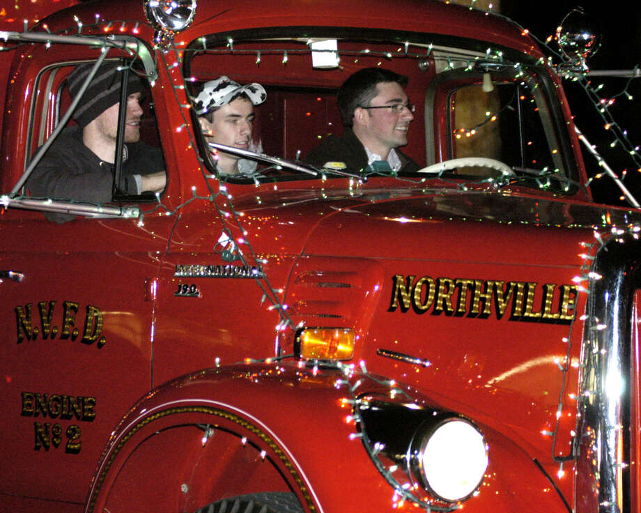 Jason Street is at the wheel of the Northville volunteer firefighters' well-decorated firetruck Saturday, Nov. 30, 2013 along the New Milford Village Green during the Greater New Milford Chamber of Commerce's annual Festival of Lights. Photo: Norm Cummings / The News-Times