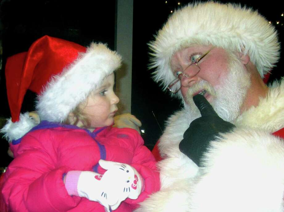 Kinsley Johnson, 2, of Washington awaits Santa Claus' considered response to her Christmas wishes Saturday, Nov. 30, 2013 on the bandstand during the Greater New Milford Chamber of Commerce's annual Festival of Lights. Photo: Norm Cummings / The News-Times
