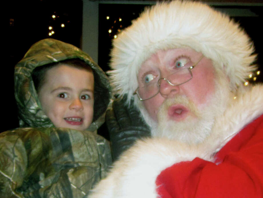 Skylar Williams, 3, of New Milford isn't sure what to make of his friend, Santa Claus, as they chat  Saturday, Nov. 30, 2013 on the bandstand during the Greater New Milford Chamber of Commerce's annual Festival of Lights. Photo: Norm Cummings / The News-Times