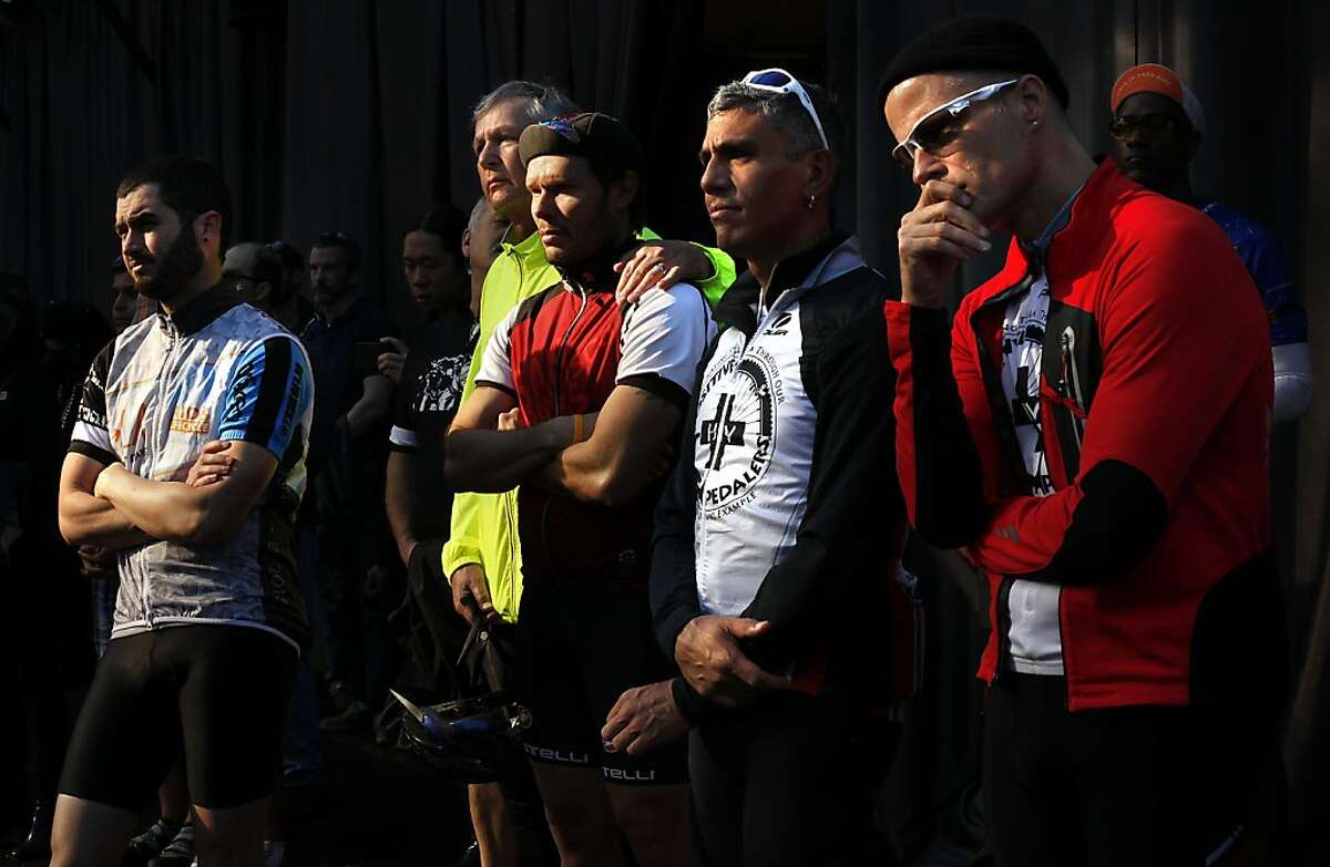 From right, Parker Trewin, Gabriel Rocha, Victor Tort, Mike Barsul, and William Torres listen to the World AIDS Day service at the National AIDS Memorial Grove in San Francisco, Calif., on Sunday, December 1, 2013. The men rode to the service with AIDS LifeCycle and Positive Pedalers.