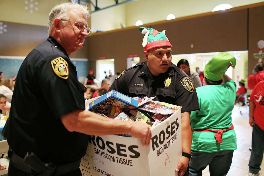 Bexar County Sheriff's Deputy Chief Joe Hamilton, left, and Lt. Henry Reyes carry a box full of toys during the Holiday Party for Children of Incarcerated Inmates at El Progreso Hall, Sunday, Dec. 1, 2013. Reyes has been promoted to the rank of deputy chief. Photo: JERRY LARA, San Antonio Express-News / © 2013 San Antonio Express-News