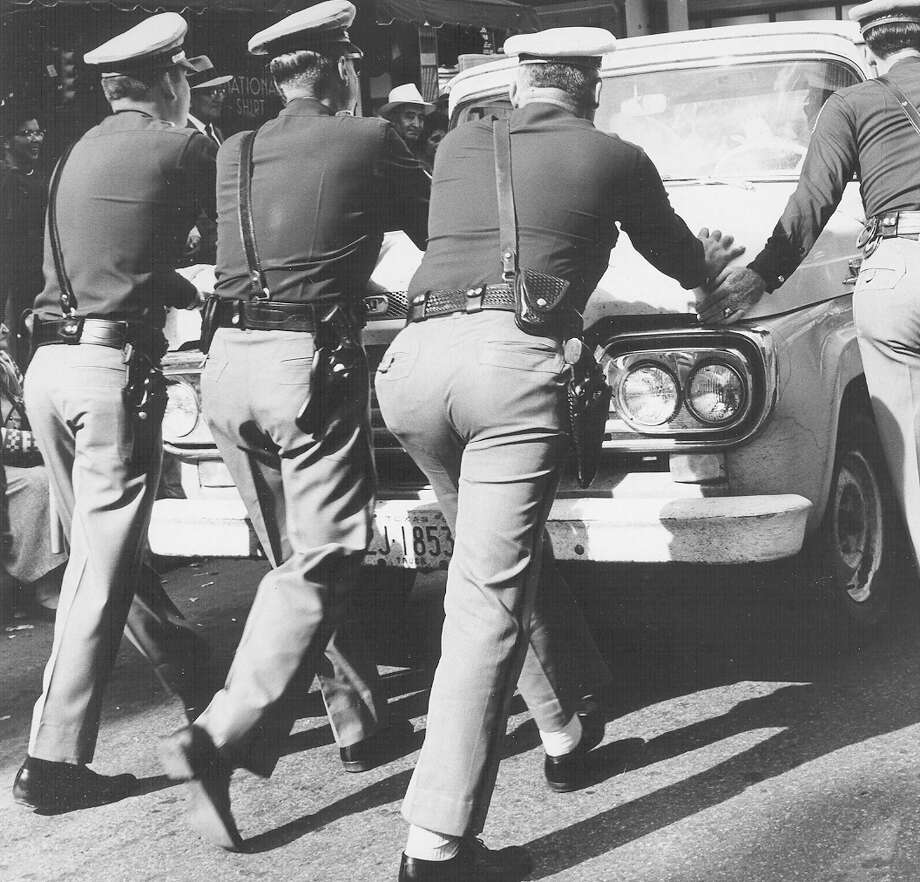 Police officers stop a vehicle during President John F. Kennedy's motorcade through San Antonio on Nov. 21, 1963, the day before he was assassinated in Dallas. Photo: San Antonio Express-News File Photo