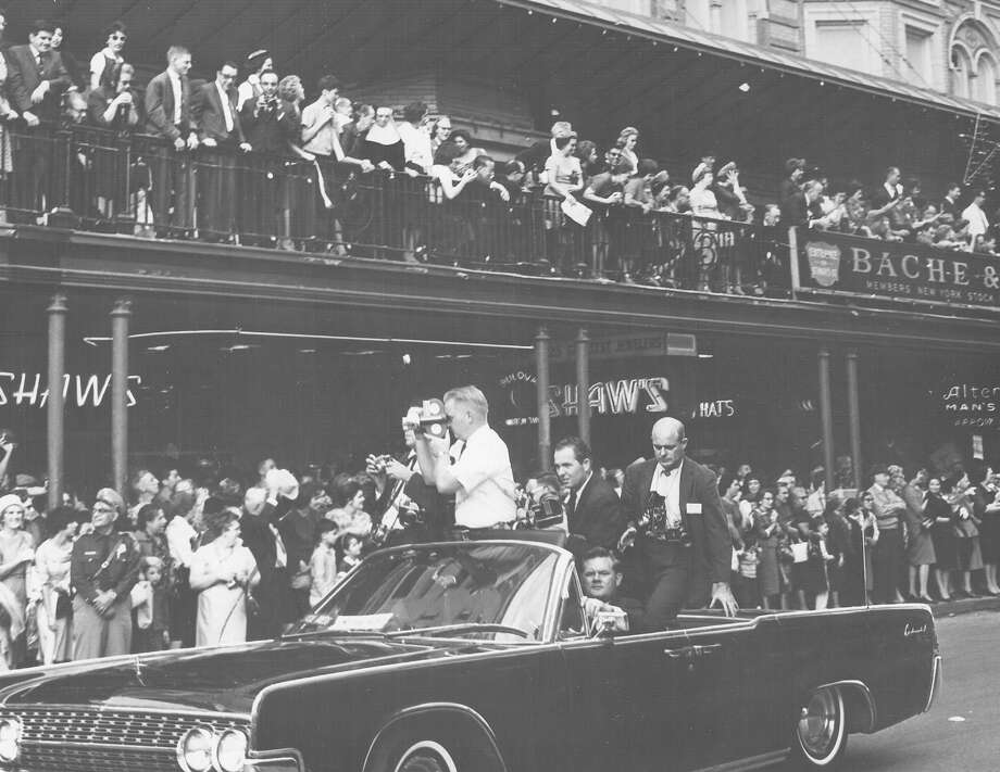 A photographer surveys the crowd as President John F. Kennedy's motorcade cruises through downtown San Antonio on Nov. 21, 1963, the day before he was assassinated in Dallas. Photo: San Antonio Express-News File Photo
