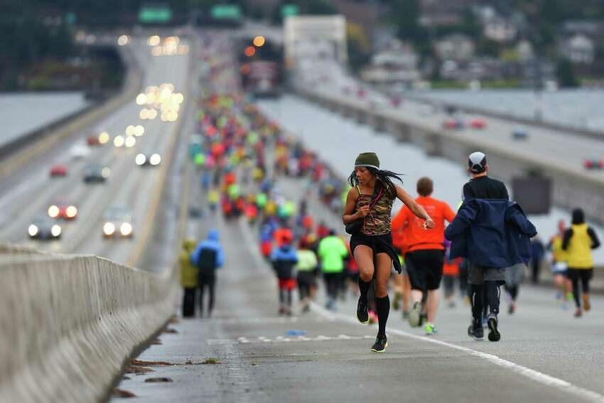 A competitor runs backwards along the length of the Interstate 90 floating bridge during the Seattle Marathon on Sunday, Dec. 1, 2013.