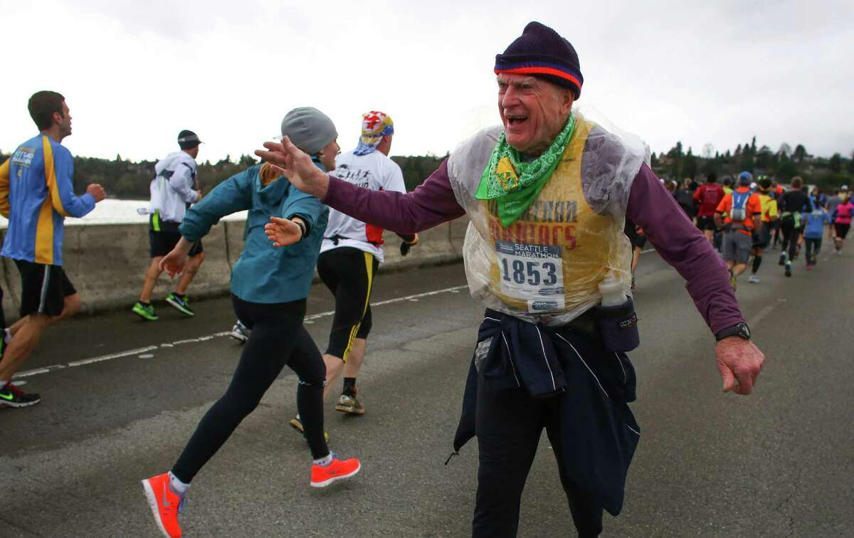 Mel Preedy gets high fives from other runners as he crosses the Interstate 90 floating bridge and completes his 438th marathon during the Seattle Marathon on Sunday, Dec. 1, 2013.