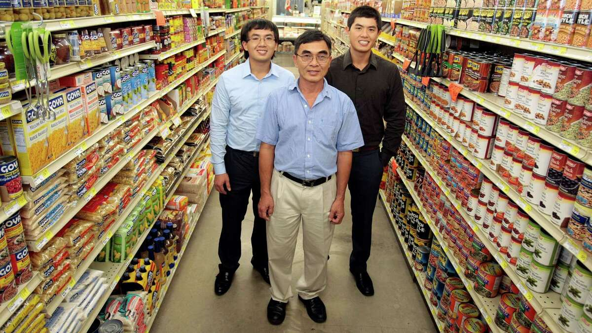 John Vuong, center, is grooming his sons, David, left, and Bob to take over his stores someday. Most of the 11 stores Bob Vuong and his family own operate in low-income, under-served areas of the city.