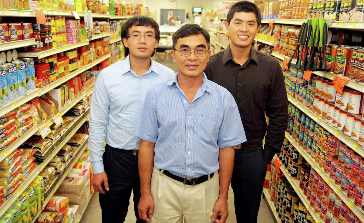 (Center) John Vuong, a Vietnamese immigrant who owns grocery stores in low-income neighborhoods with his two sons (l-r) David and Bob Vuong October 30, 2013 at Pyburn's supermarket in Houston, TX. (Billy Smith/Houston Chronicle)