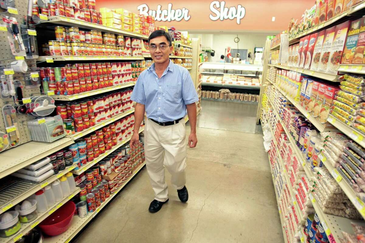 (Center) John Vuong, a Vietnamese immigrant who owns grocery stores in low-income neighborhoods at his supermarket Pyburn's s in Houston, TX. (Billy Smith/Houston Chronicle)