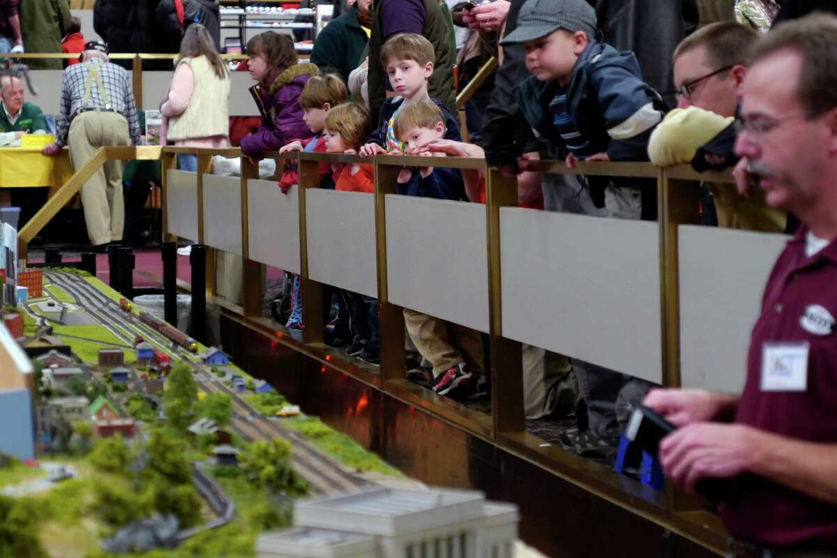 Children watch as model train hobbyists work a train around the tracks at the Great Train Extravaganza 2013 at the Empire State Plaza Convention Center on Sunday, Dec. 1, 2013 in Albany, NY. The annual event is put on by the Hudson-Berkshire Division of the National Model Railroad Association and The Upstate Train Association. The event features working model railroad displays along with vendors selling items from model railroad cars and engines to railroad signage and books. (Paul Buckowski / Times Union)