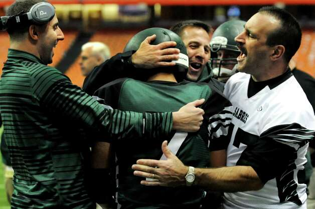 Schalmont coaches embrace Trevon Perez-Tucker, center, after scoring a touchdown on a  punt return during their Class B state football final against Maine-Endwell on Sunday, Dec. 1, 2013, at the Carrier Dome in Syracuse, N.Y. (Cindy Schultz / Times Union) Photo: Cindy Schultz / 00024837A