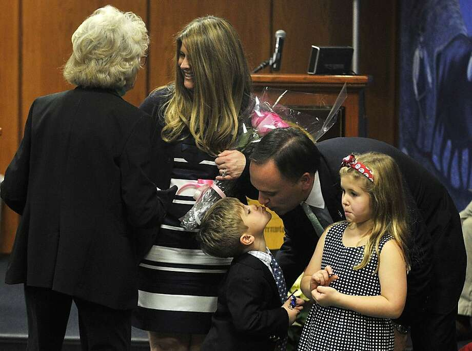 First Selectman Peter Tesei kisses his son James as his daughter, Caroline, looks on while his wife, Jill, talks with Rebecca Breed after Breed swore in Peter during the swearing in ceremony at Greenwich Town Hall in Greenwich, Conn., on Sunday, Dec. 1, 2013. Photo: Jason Rearick