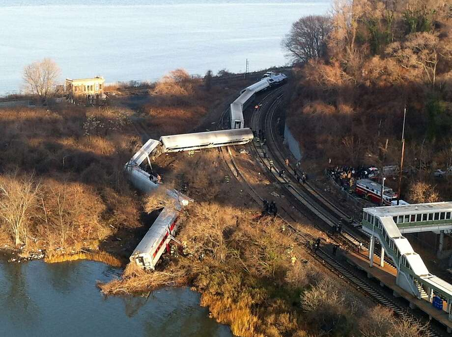 "Cars from a Metro-North passenger train are scattered after the train derailed in the Bronx neighborhood of New York, Sunday, Dec. 1, 2013. The Fire Department of New York says there are ""multiple injuries"" in the  train derailment, and 130 firefighters are on the scene. Metropolitan Transportation Authority police say the train derailed near the Spuyten Duyvil station.  Photo: Edwin Valero, Associated Press"