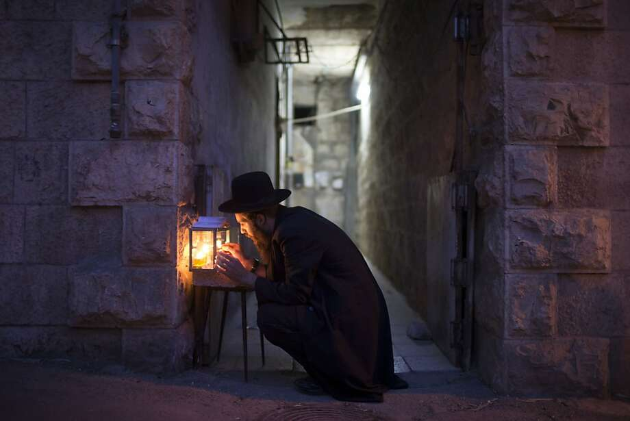 A Jewish man prays and lights candles on the fifth night of the Jewish holiday of Hanukkah, the festival of 