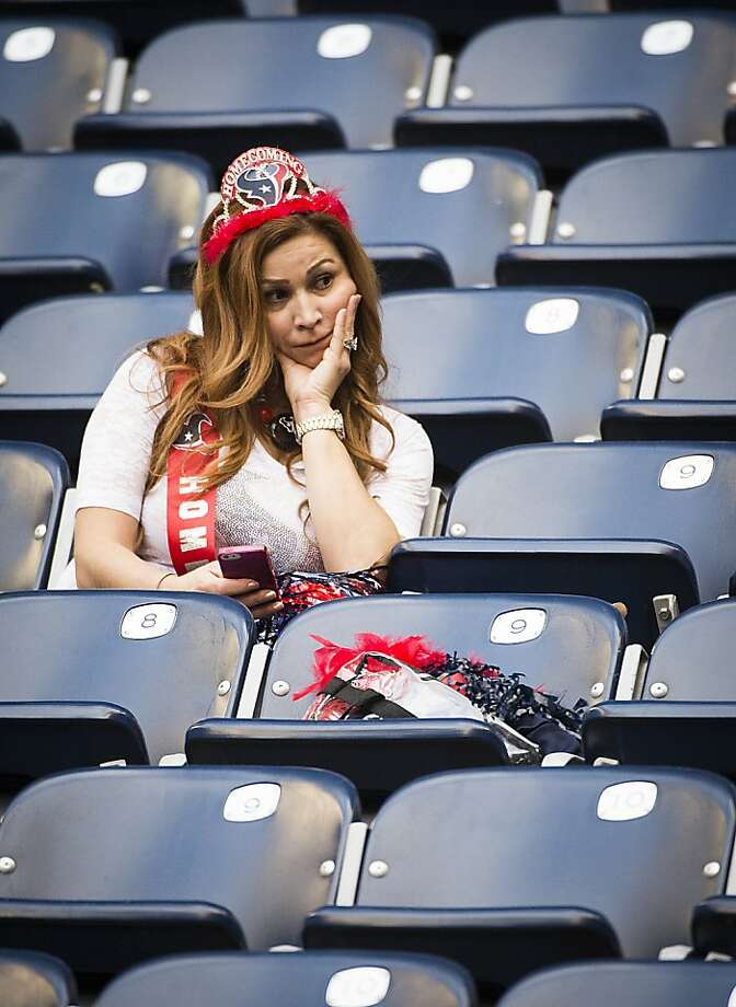 "A Houston Texans fan dresses as a Homecoming Queen sits in the stand after the Texans 34-31 loss to the New England Patriots in a game the team pegged with the theme ""Homecoming"" after an NFL football game at Reliant Stadium on Sunday, Dec. 1, 2013, in Houston. Photo: Smiley N. Pool, Houston Chronicle"