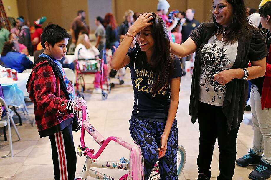 Sunshine Rodriguez, 13, sits on her bicycle she won as the first door prize of the Holiday Party for Children of Incarcerated Inmates at El Progreso Hall, Sunday, Dec. 1, 2013. The event featured door prizes and gifts for the children as well as a tamale dinner. The event was the effort of Bexar County Sheriff's Department employees who donated their time and solicited donations from the business community. No taxpayer's monies were used in the event. Her mother, Patricia Martinez is on the right and her brother, Thomas Rodriguez, 10, is on the left. Photo: Jerry Lara, San Antonio Express-News