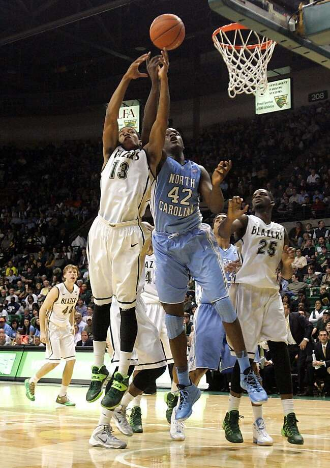 UAB guard Chad Frazier (left) and North Carolina forward Joel James vie for a rebound during the second half. Frazier scored 25 points to lead the Blazers to an upset on their homecourt in a game that pitted Carolina's Roy Williams against his protege, Jerod Haase. Photo: Butch Dill, Associated Press