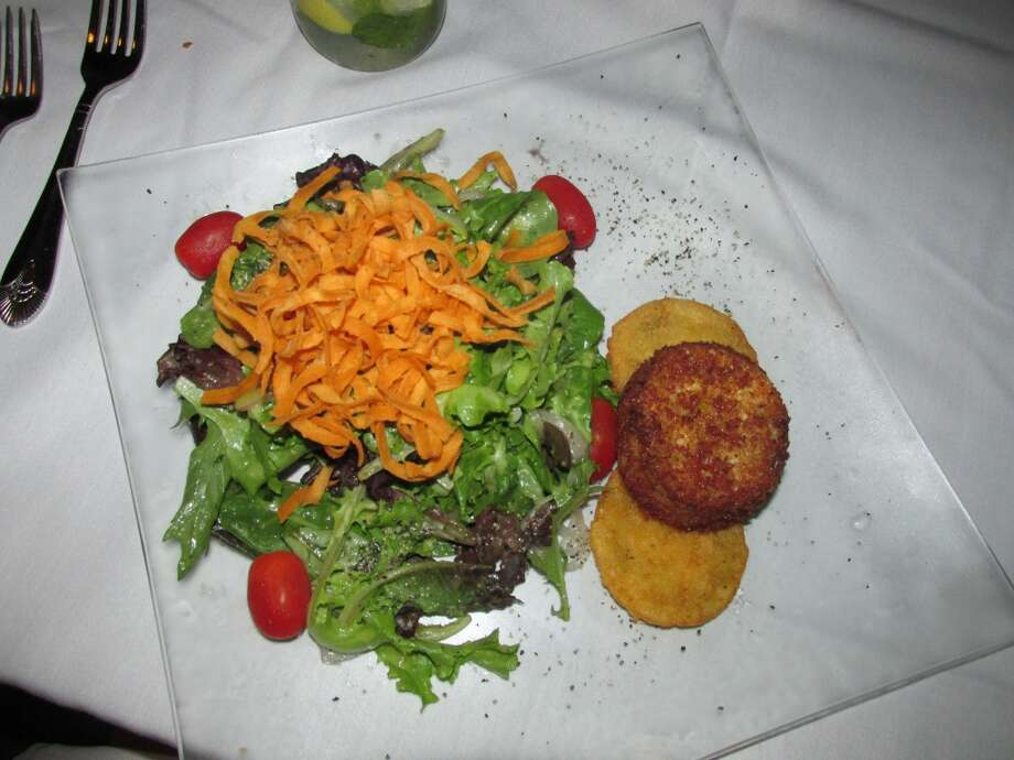 Suga's crab cake salad, made with house-made lump crab cakes on a bed of fried green tomatoes, red onions, cherry tomatoes, mixed greens and Georgia peach vinaigrette. Photo: Cat5