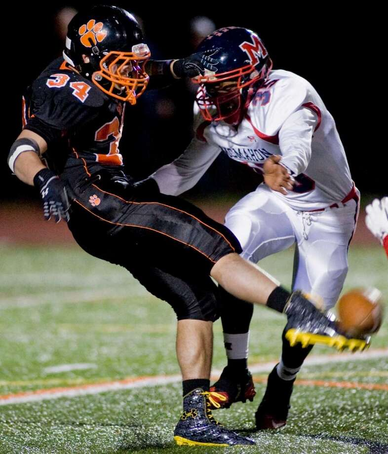 Ridgefield High School's Will Bonaparte gets off a punt before being hit by McMahon High School's Allan Lenard during a game at Ridgefield. Friday, Nov. 8, 2013 Photo: Scott Mullin