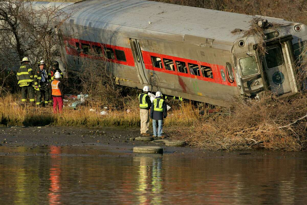 Officials with the National Transportation Safety Board inspect a derailed Metro North commuter train where it almost fell into the Harlem River, Sunday, Dec. 1, 2013 in the Bronx borough of New York. The Metro-North train derailed on a curved section of track early Sunday, coming to rest just inches from the water, killing four people and injuring more than 60, authorities said.