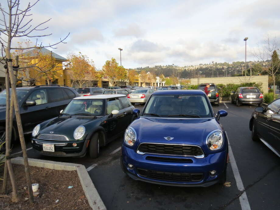 The 2013 Mini Cooper Paceman (right) next to a stock Mini Cooper. The Mini Cooper line has grown since the remake of the original Mini was introduced in 2000.   (All photos by Michael Taylor)