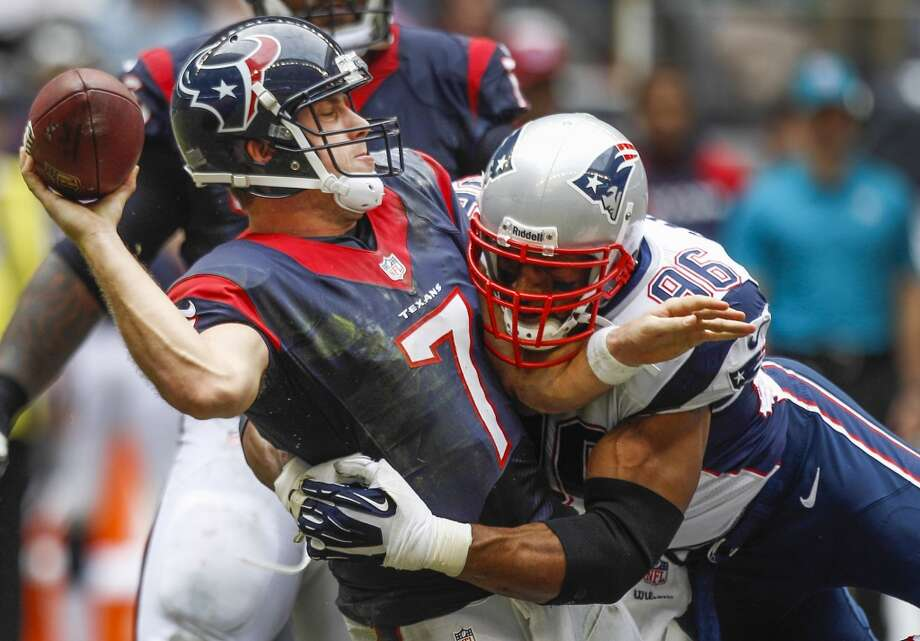 Texans quarterback Case Keenum is hit by Patriots defensive end Andre Carter as he releases the ball for an incomplete pass on fourth down during the fourth quarter. Photo: Brett Coomer, Houston Chronicle