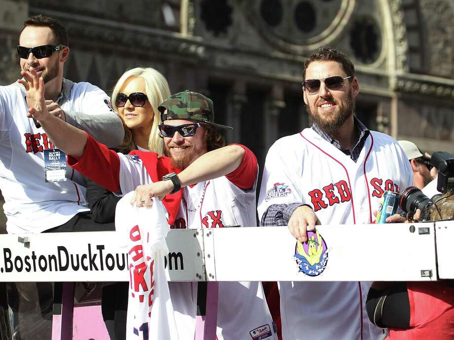 Clay Buchholz (center)  and John Lackey (right) wave from one of the duck boats as they make their way down Boylston Street where fans gathered for the World Series victory parade for the Boston Red Sox in Boston, Massachusetts.  (Photo by Gail Oskin/Getty Images) Photo: Gail Oskin, Stringer / Getty Images