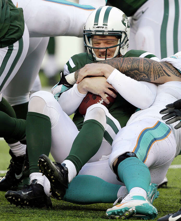 New York Jets quarterback Matt Simms, center, is sacked by Miami Dolphins outside linebacker Koa Misi during the second half of an NFL football game on Sunday, Dec. 1, 2013, in East Rutherford, N.J. Photo: Seth Wenig, ASSOCIATED PRESS / AP2013