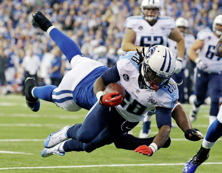 Tennessee Titans' Chris Johnson (28) dives while being tackled by Indianapolis Colts' Cory Redding during the first half of an NFL football game Sunday, Dec. 1, 2013, in Indianapolis. Photo: Michael Conroy, ASSOCIATED PRESS / AP2013