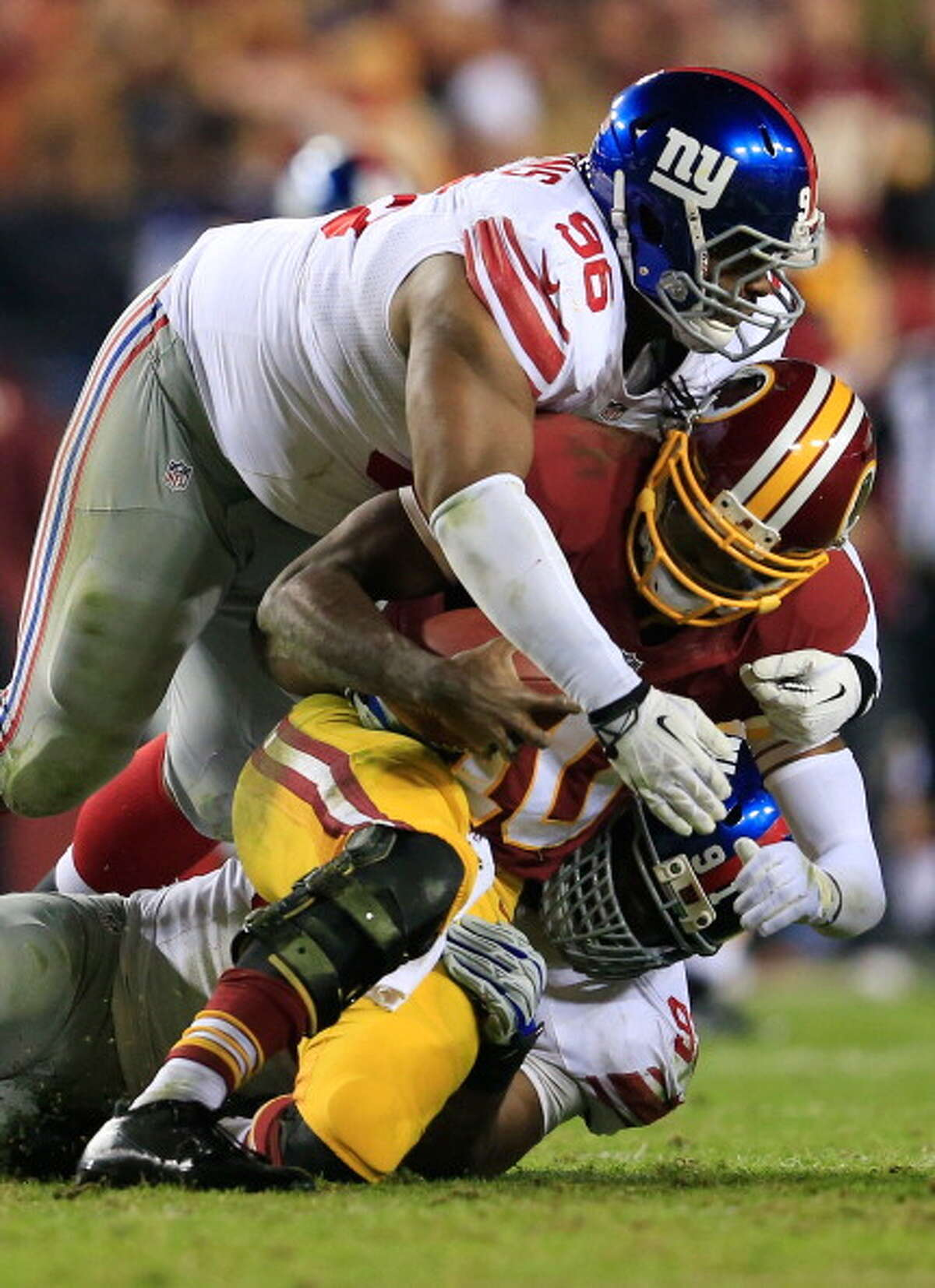 LANDOVER, MD - DECEMBER 01: Defensive end Justin Tuck #91 and defensive tackle Johnathan Hankins #96 of the New York Giants sack quarterback Robert Griffin III #10 of the Washington Redskins during the fourth quarter of the Giants 24-17 win at FedExField on December 1, 2013 in Landover, Maryland.