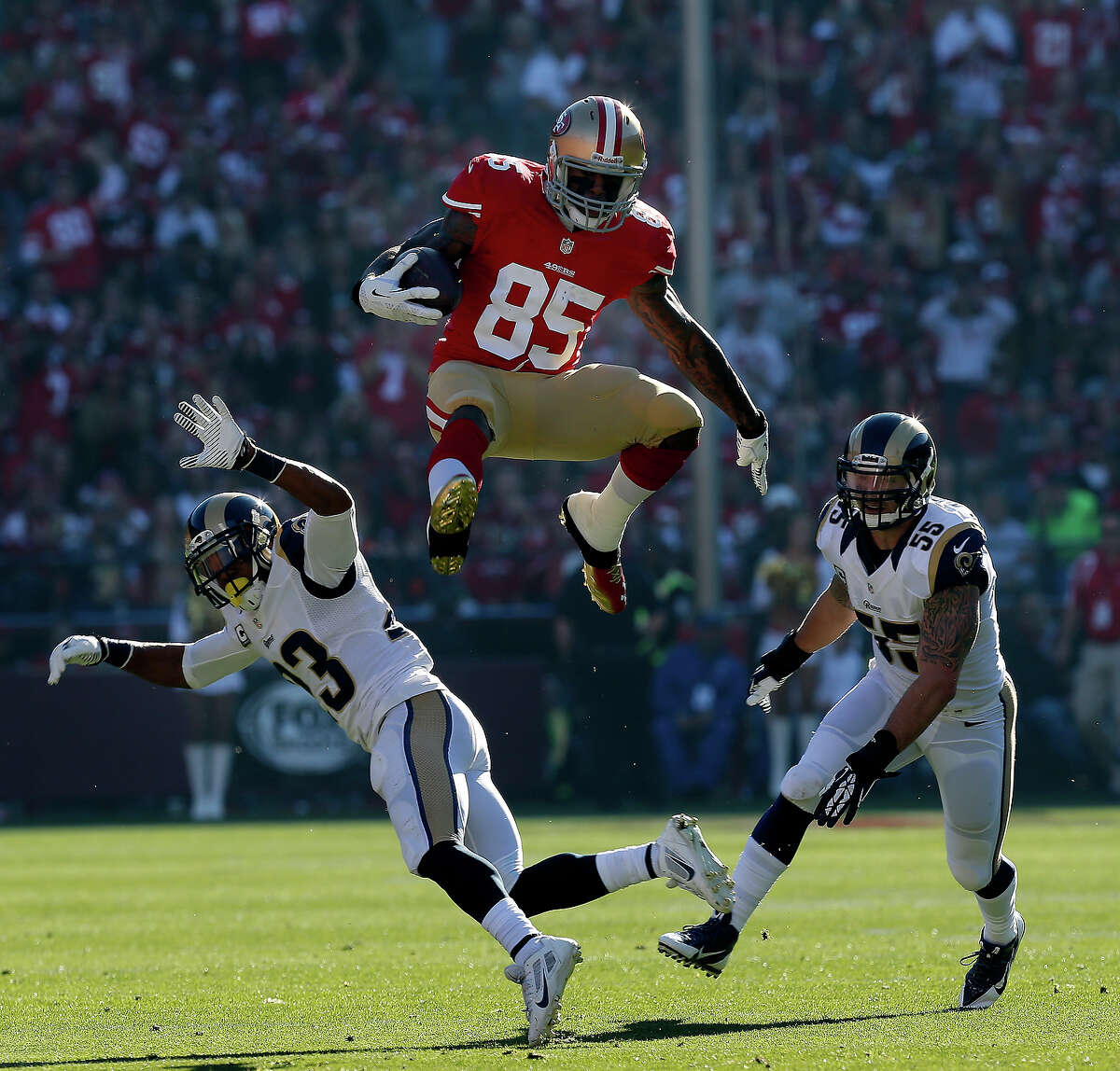 Vernon Davis goes high over two defenders in a big catch in the first half. The San Francisco 49ers vs the St. Louis Rams at Candlestick Park Sunday December 1, 2013.