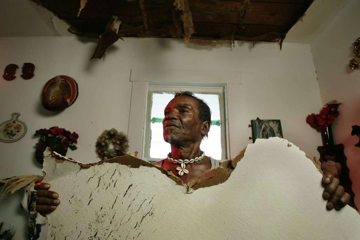 Cleveland Turner holds part of the ceiling inside his home that collapsed from the effects of Hurricane Ike Oct. 2, 2008 in Houston. Hurricane Ike damaged the house of African yard artist Cleveland Turner, aka The Flower Man. The orange show foundation is calling for a Saturday work day to make repairs. Oct. 2, 2008 ( Eric Kayne / Chronicle )