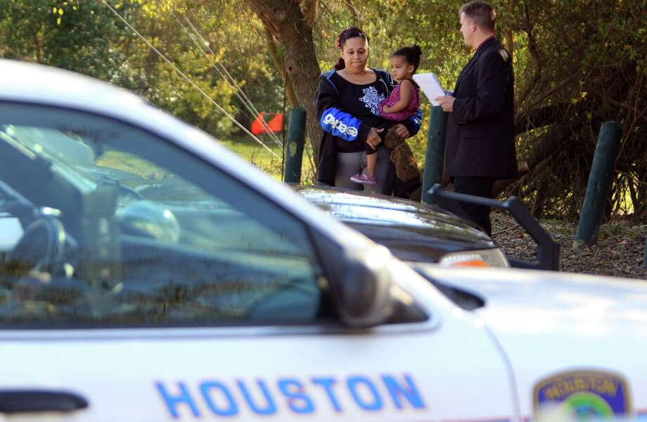 Chandra Lopez carries daughter Zariyah, 2, as she gives information to HPD Homicide Investigator K. McDonald of suspicious activity the morning students from MacArthur High School cross country team found the lifeless body of a 17-year-old Hispanic male while running through Keith-Weiss Park on Monday, Dec. 2, 2013, in Houston. Photo: Mayra Beltran, Houston Chronicle / © 2013 Houston Chronicle