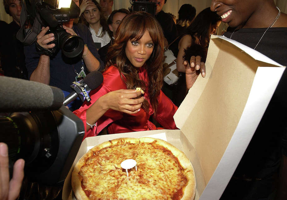 Tyra Banks helps herself to some New York pizza before the 8th Annual Victoria's Secret Fashion Show in 2002. Photo: KMazur, WireImage / WireImage