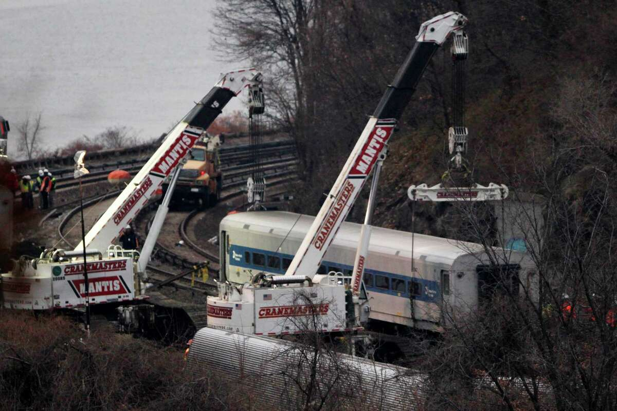 """Cranes lift a derailed Metro-North train car, Monday, Dec. 2, 2013, in the Bronx borough of New York. Federal authorities began righting the cars Monday morning as they started an exhaustive investigation into what caused a New York City commuter train rounding a riverside curve to derail, killing four people and injuring more than 60 others. A second """"event recorder"""" retrieved from the train may provide information on the speed of the train, how the brakes were applied, and the throttle setting, a member of the National Transportation Safety Board said Monday. (AP Photo/Mark Lennihan) ORG XMIT: NYML101"""