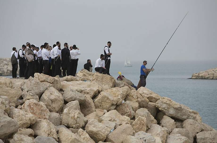 This is so exciting ... A group of ultra-Orthodox Jews watch a lone fisherman try to hook one off a stone pier in Tel 