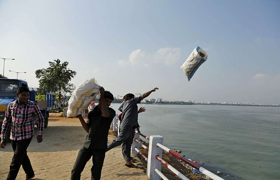 Visit India's lovely garbage lake!The promenade of Hussainsagar Lake in Hyderabad is a busy thoroughfare, providing boating and water sports and, apparently, waste disposal. At least that's what these men were using it for. Photo: Rajesh Kumar Singh, Associated Press