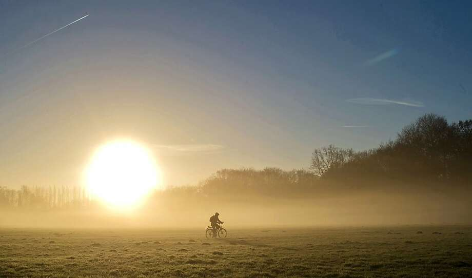 Fog, calories burning off:A cyclist rides through a park in Berlin at sunrise. Photo: Tim Brakemeier, Associated Press