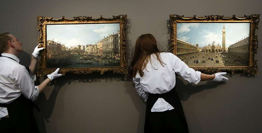 "Venice, anyone? Sotheby's employees hang ""A View of the Grand Canal and Rialto Bridge"" (left) and ""A View of 