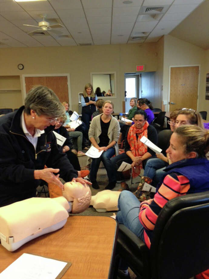 Joan Gildea, Darien EMS-Post 53 adult advisor and CPR director, teaches the staff at Playdates Preschool CPR, AED and first aid. Photo: Contributed Photo, Contributed / Darien News