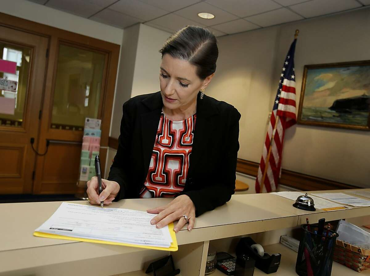 At the Oakland, Calif. city clerk's office, Libby Schaaf completes the paperwork for her run for mayor Monday December 2, 2013. Oakland City Council member Libby Schaaf filed papers to run for mayor of Oakland.