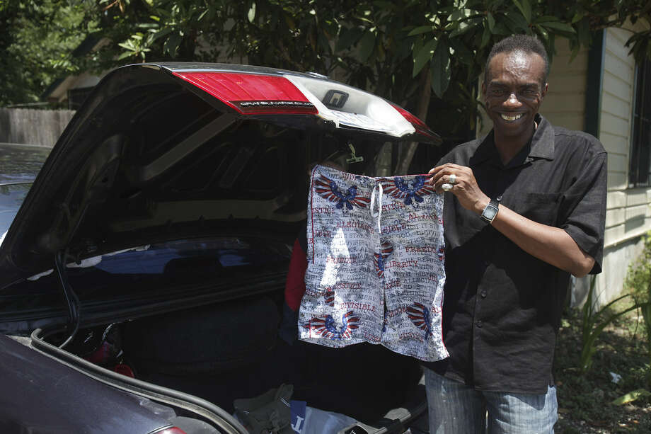 Willie Rucker, who founded Rucker Helping Kids and Youth to the Next Level, shows some of the donated clothes he  gathered for East Side youth this year. Photo: San Antonio Express-News