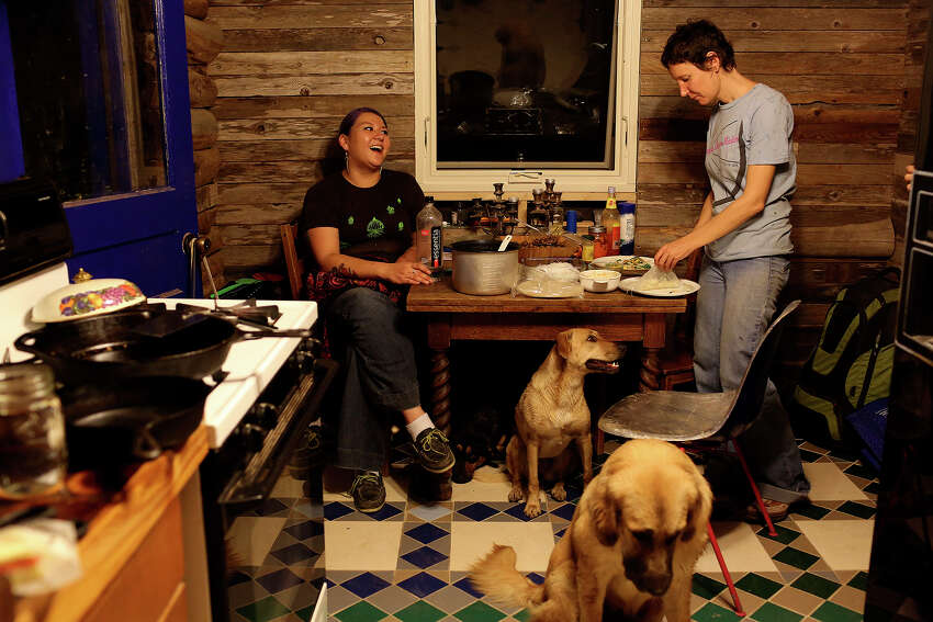 Artist-in-residence Laura Napier, right, and outreach coordinator Christina Lee Shane finish dinner after rain brought their outdoor meal inside with dogs Lilly and Mina, front, at Habitable Spaces in Kingsbury on Thursday, Nov. 21, 2013.